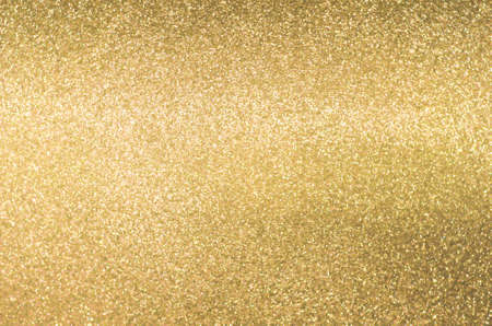 Gold texture background with yellow luxury shiny shine glitter sparkle of bright light reflection on golden surface, for celebration backdrop, wallpaper, Christmas decoration background or any design