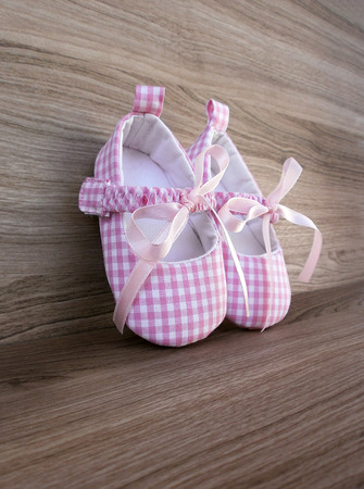 Cute pink baby girl shoes on wooden background  photo