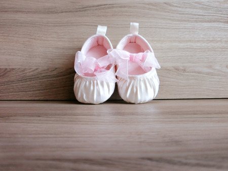 Baby girl shoes on wooden background  photo
