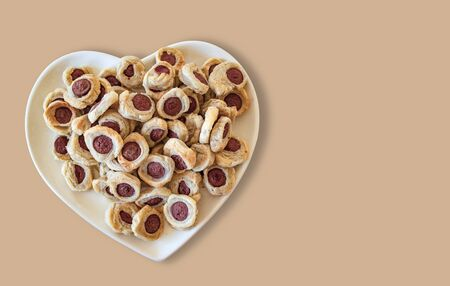 pastry and mini hot dogs in heart-shaped plate, on wooden table background.