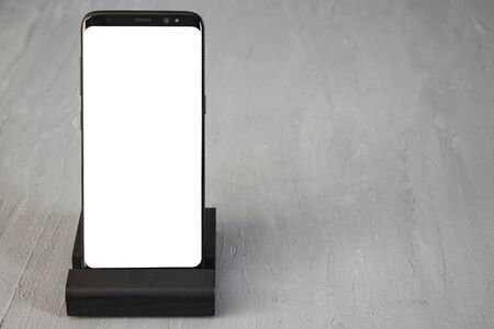 Modern smartphone mockup blank empty screen on desk table in isolated background.