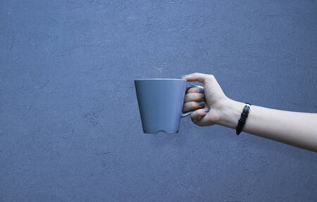 Mockup of female hand holding a coffee cup isolated on blue background.