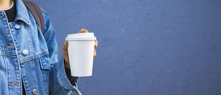 Mockup of female hand holding a Coffee paper cup isolated on blue background.