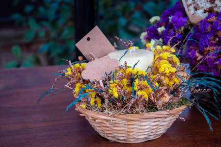 Beautiful flowers in the flowerpot with a label on it, in a natural garden