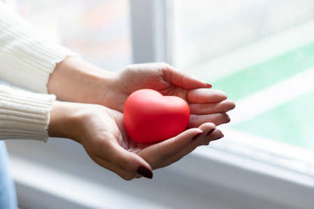 A woman holding a red heart between her hands. Happy valentine's day, red color, heart icon, isolated background