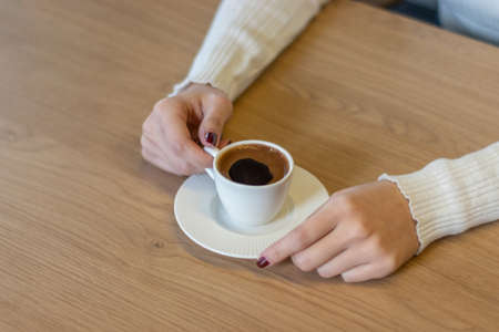 The woman on the wooden table holding Turkish coffee with your hands 免版税图像