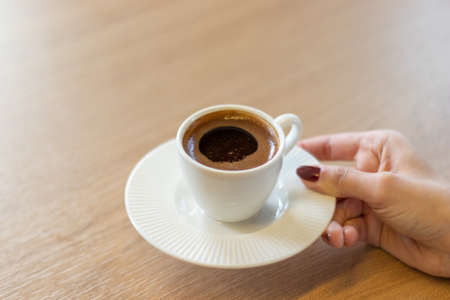 The woman on the wooden table holding Turkish coffee with hands