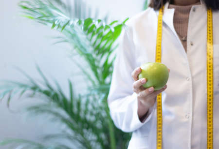 female dietitian in apron and tape measure holding apple