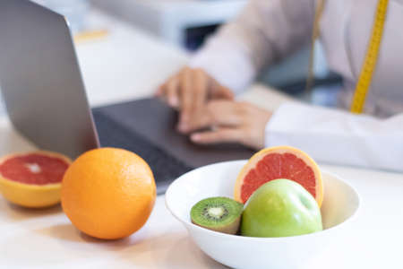 dietitian woman working with her computer and an office with mixed fruit and water on the table 免版税图像