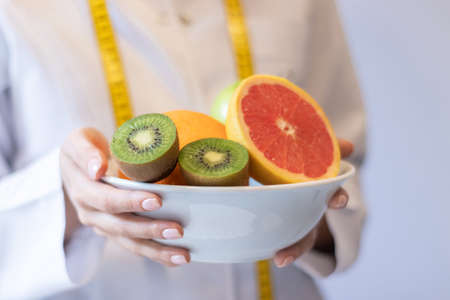 nutritionist holding bowl of mixed fruit 免版税图像