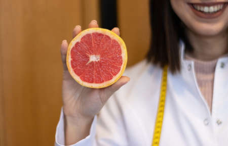 female nutritionist in apron and tape measure holding grapefruit