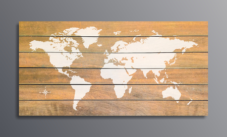world map on a background texture of wooden planks on grey wall.