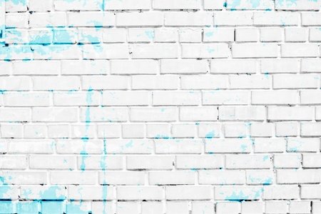 closeup of white brick wall with blue paint stains photo