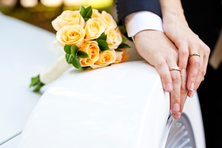 Hände von Braut und Bräutigam mit Ringen und Blumenstrauß