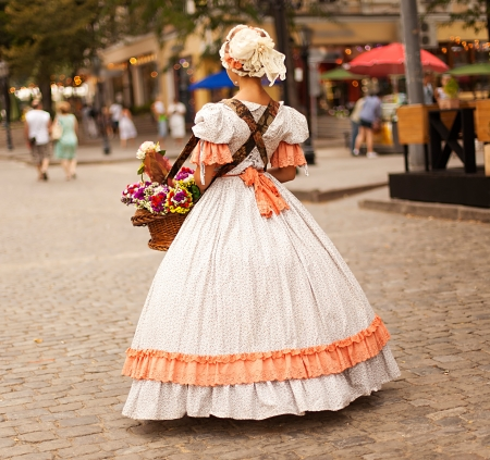 medieval dress: medieval women from back with flowers in hands on a modern street  Stock Photo