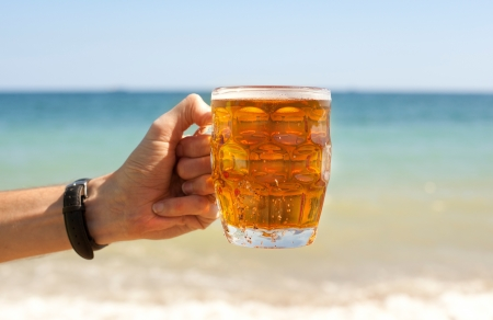 Mug of beer in hand on beach photo