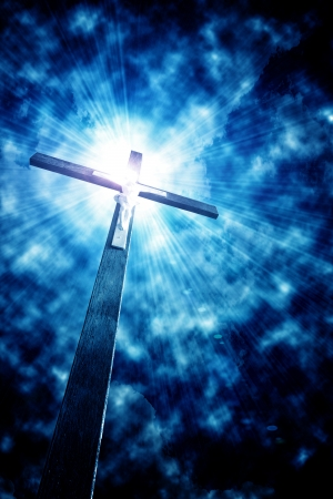 religious life: cross in sunrays against cloudy sky