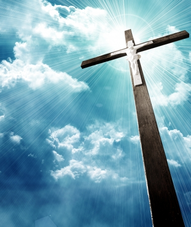 christian symbol: cross in sunrays against cloudy sky