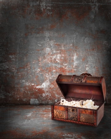 treasure chest with jewelry inside against grunge background photo
