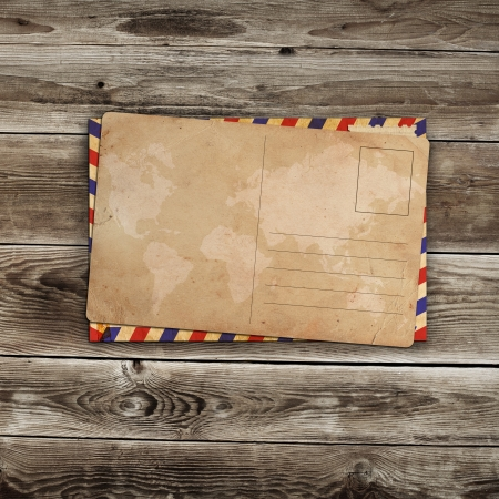 vintage postcard with envelop on wooden background