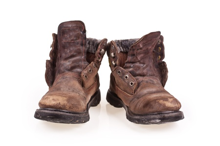 Dirty old boots isolated over white background photo