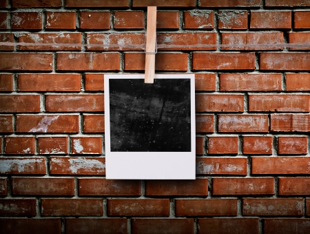 Photo frame with pins on rope over old aged brick wall photo