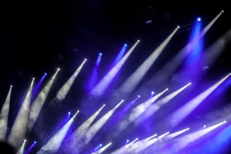 明るいステージ ライトの前で歓声を上げる群衆