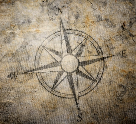 lost world: Old compass on paper background
