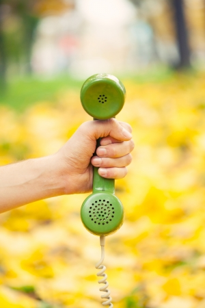 hand holding vintage phone receiver in autumn park photo