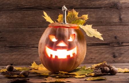 jack-o-lantern with leaves on wooden background photo