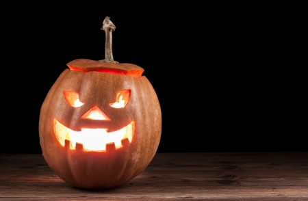 dark scary jack-o-lantern on wood photo
