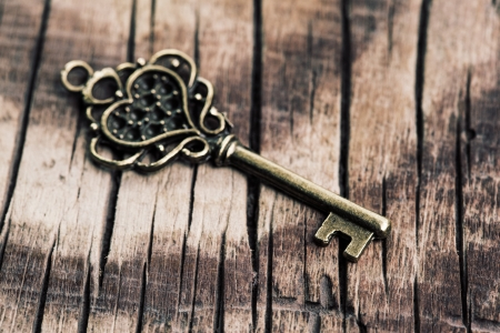 Vintage key on wooden background photo