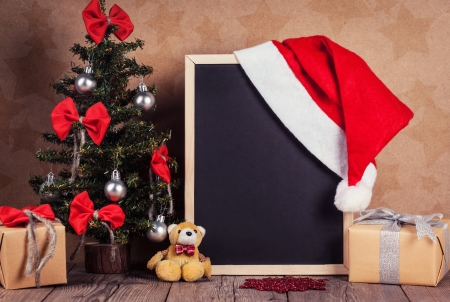 blank blackboard with Santa hat and christmas decoration photo