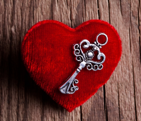 vintage key and red heart on wooden background photo