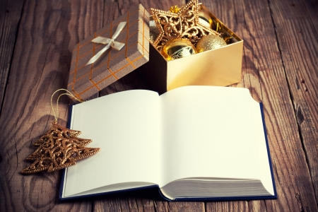 open book with christmas decoration on wooden background photo