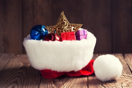 christmas decoration in Santas hat on wooden background photo