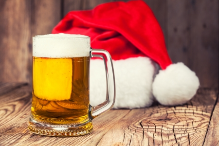 mug of beer with Santas hat on wooden background Stock Photo