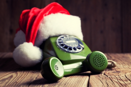 vintage phone with Santas hat on wooden background photo