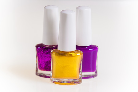 Purple and gold nail polish on a white  photo