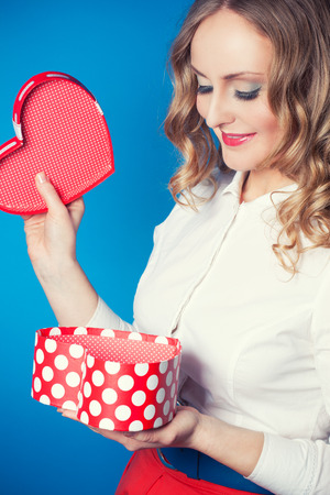 Young woman holding heart-shaped gift box photo