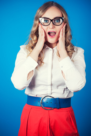 Surprised woman in glasses on blue wall photo