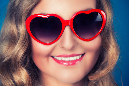 Young blonde woman with heart shaped glasses photo