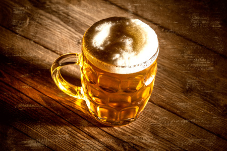 un bottled: Mug of beer on wooden table  with vintage scratches