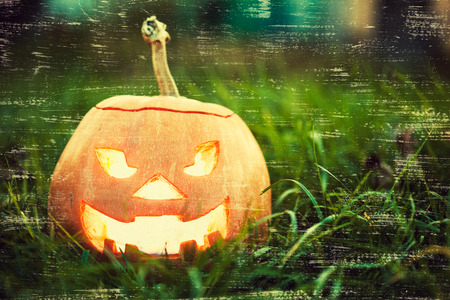halloween jack-o-lantern on green grass with vintage scratches photo