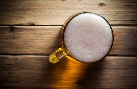 Mug of beer on wooden background photo