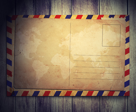 manila envelop: vintage postcard with envelop on wooden background