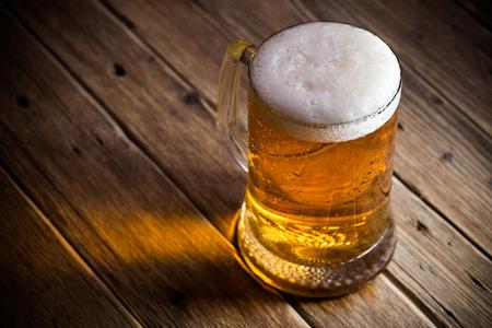 木製の背景にビールのジョッキ 写真素材