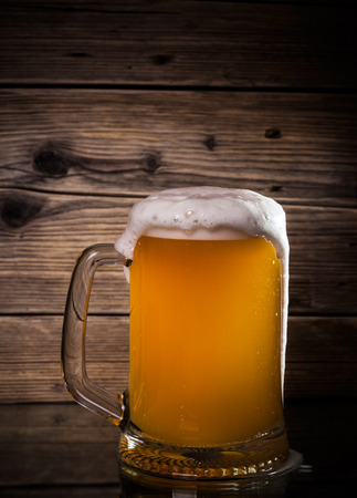 wino: glass beer on wood background