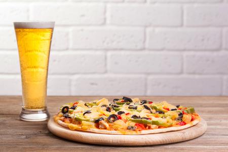 ビールのガラスのテーブルの上のピザ