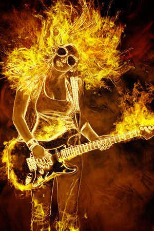young woman with guitar in fire flames on black background